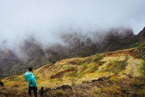 Panoramic shot of traveler taking picture of amazing steep mountain range and terrain canyon valley on the path from Xo-Xo Valley. Camera on tripod.Santo Antao Island, Cape Verde