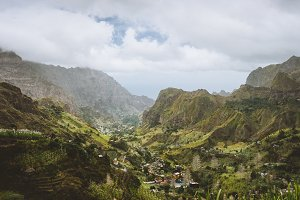 Cape Verde. Gorgeous panoramic view of famous fertile Paul Valley. Agriculture terraces of sugarcane in vertical valley sides, people dwellings, rugged peaks and motion clouds on horizon