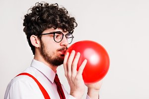 Portrait of a young man with balloon in a studio.