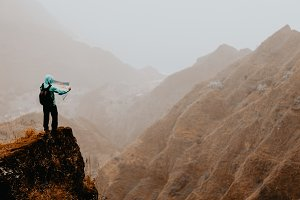 Hiker with map in steep rocky terrain in front of a incredible panorama view of high mountain ranges deep ravines and coastline. Santo Antao Cape Verde