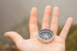 Hand with compass in the misty mountain terrain
