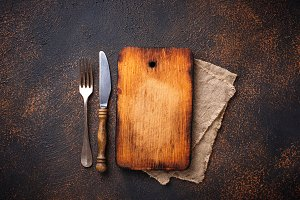 Empty vintage cutting board with fork and knife