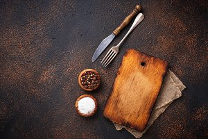 Empty vintage cutting board with spices and cutlery
