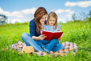 Mother and daughter reading book on green summer meadow