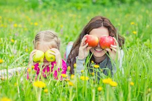 Mother and daughter on sunny meadow with apples in hands