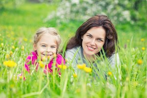 Mother and daughter on green summer meadow