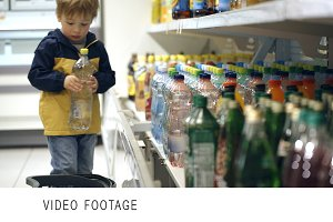 Little boy putting mineral water