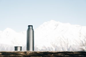 Thermos with cup in winter outdoor.