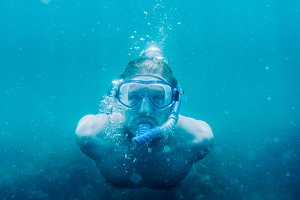 Male freediver swimming underwater.