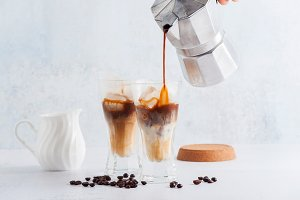Pour milk in cold brew coffee on the
