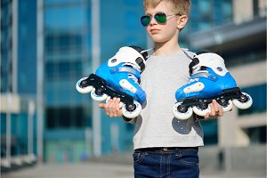 Young beautiful boy with roller skates in his hands