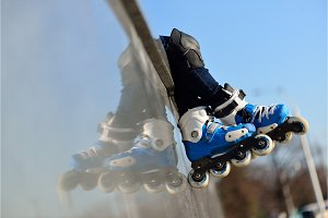 Feet of group childrens wearing inline roller skates sitting in outdoor skate park, Close up view of wheels befor skating