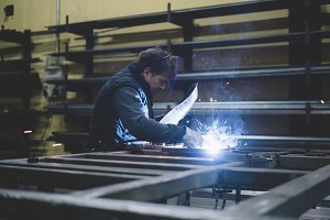 Man working in welding workshop.