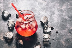 Refreshing red drink on a dark background, space for text.