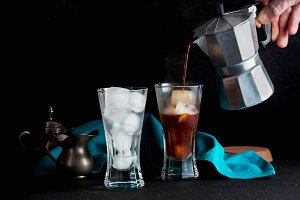man's hand pours coffee in glasses w