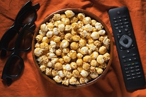Wooden bowl with sweet popcorn, TV remote control and 3D glasses on orange bedding. Top view. Snacks and food for a movie