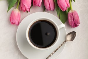 Black coffee in white Cup with pink tulips on light stone background. Top view with copy space