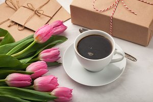 Pink tulips, a cup of coffee and a gift on a light stone background. Concept of Spring
