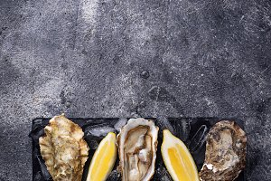 Fresh oysters with lemon on dark background
