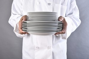 Chef Carrying Stack of Plates
