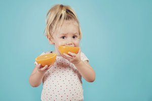 baby eating an orange