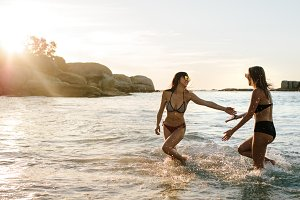 Female friends playing in sea water