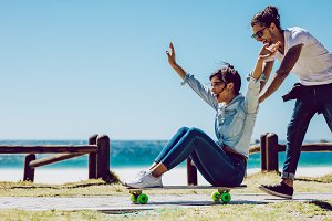 Loving couple playing on skateboard