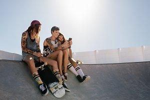 Female skaters using smart phone