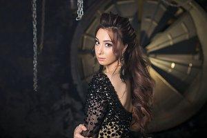 Fashion studio photo of gorgeous sensual latina woman with dark hair in luxurious dress with rhinestones looking to camera. Dark loft studio interior