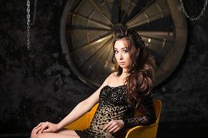 Sexy brunette woman in evening cocktail dress in dark studio interior
