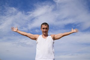man in a white T-shirt laid his hands wide against the blue sky with clouds.