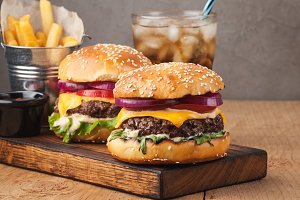 Close-up of delicious fresh home made burger with lettuce, cheese, onion and tomato on a rustic wooden plank on a dark background. Also fries and Cola with ice
