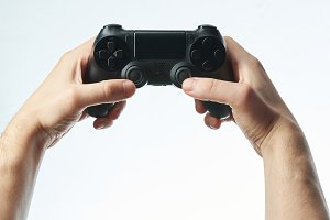 Hands holding black game controller