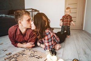 Mom kisses dad on the floor in the nursery