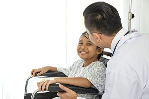 Male asian doctor touching pediatric patients
