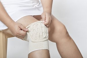 woman sit wearing a knee support for healing injury