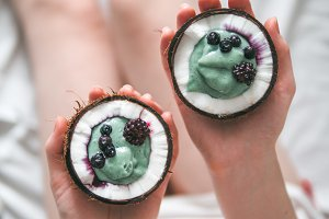 Two coconut half spirulina smoothie in woman hands
