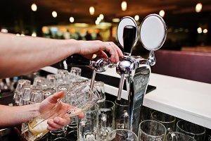 Close up of barman hand at beer tap