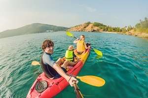 happy family with kid kayaking at tropical ocean