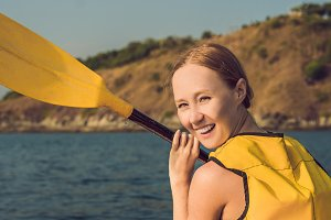 Smiling young woman kayaking on sea. Happy young woman canoeing in sea on a summer day