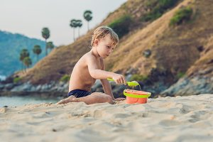 Kid playing on the seashore with shovel and bucket