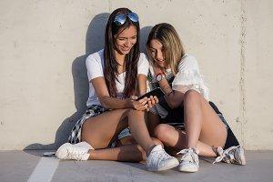 Stylish girls watching phone on pave