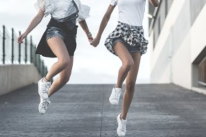 Laughing girls holding hands and run