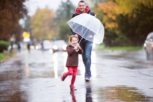 Father with little daughter under umbrella. Walk on rainy day.