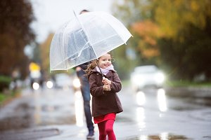 Little girl with umbrella. Walk on rainy day.