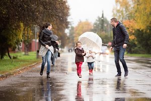 Family with daughters under the umbrellas, running. Rainy day.