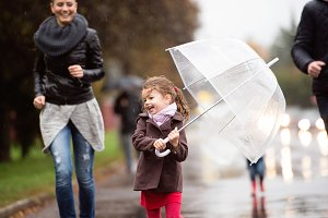 Little girl under the umbrella with her family, running. Rainy d