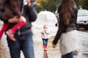 Little girl under the umbrella with her family, walking. Rainy d