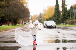 Little girl playing with transparent umbrella outside, rainy day