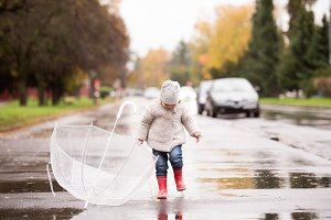 Little girl with umbrella jumping in a puddle, rainy day.